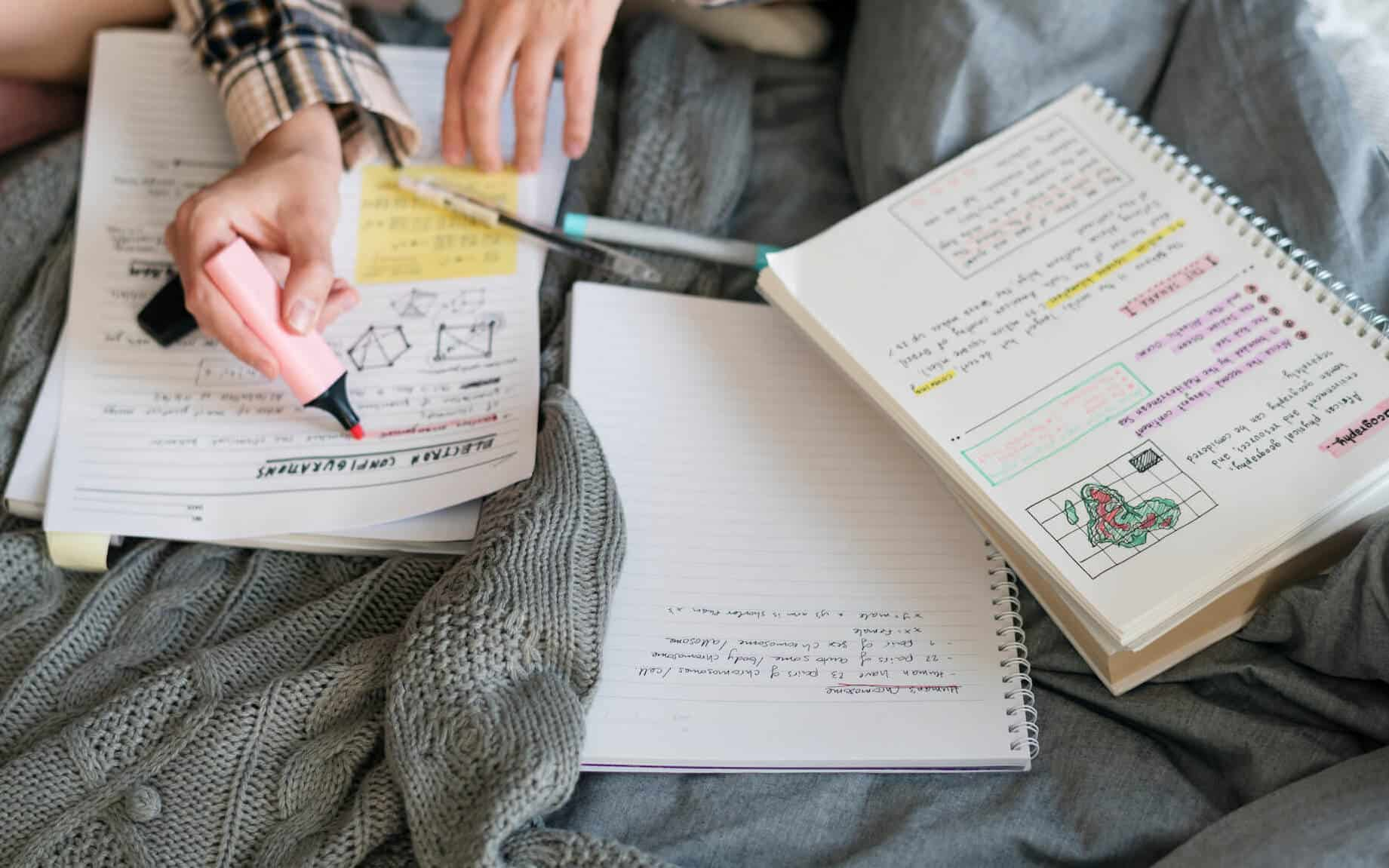 Student studies for exam, with numerous notebooks on her bed