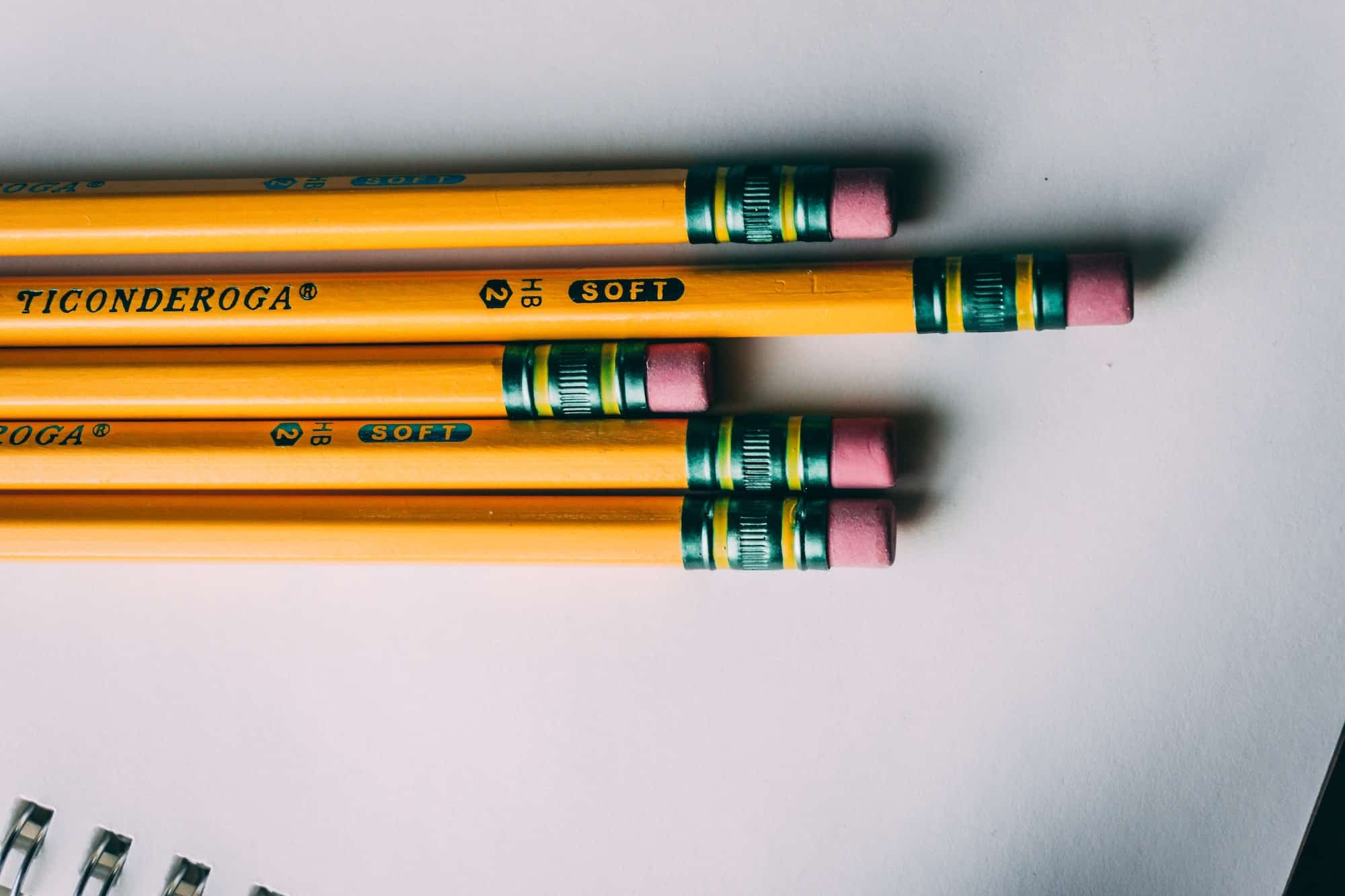 Five pencils on a blank notebook