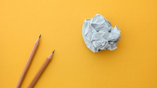 Two pencils and crumpled paper ball against yellow background