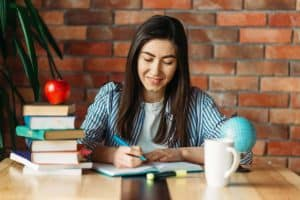 Smiling Female Student Writing in Notebook