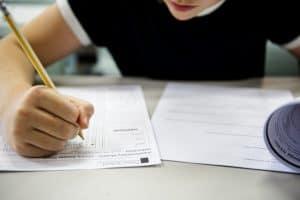 Student writing on exam