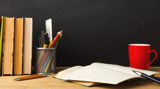 Books and pencil against chalkboard background