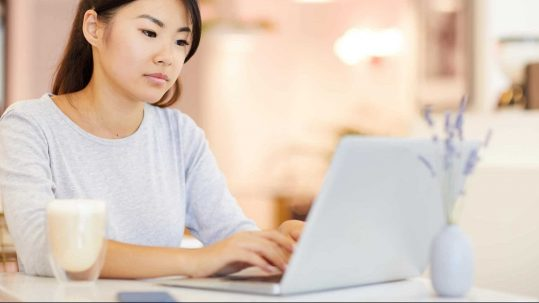 Girl sitting at table with laptop