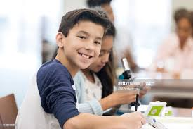 Smiling boy completing assignment